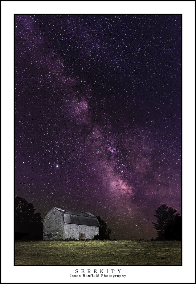 Panoramic lanscape of the Milky Way galaxy rising behind an old barn in Conquerall Mills Nova Scotia