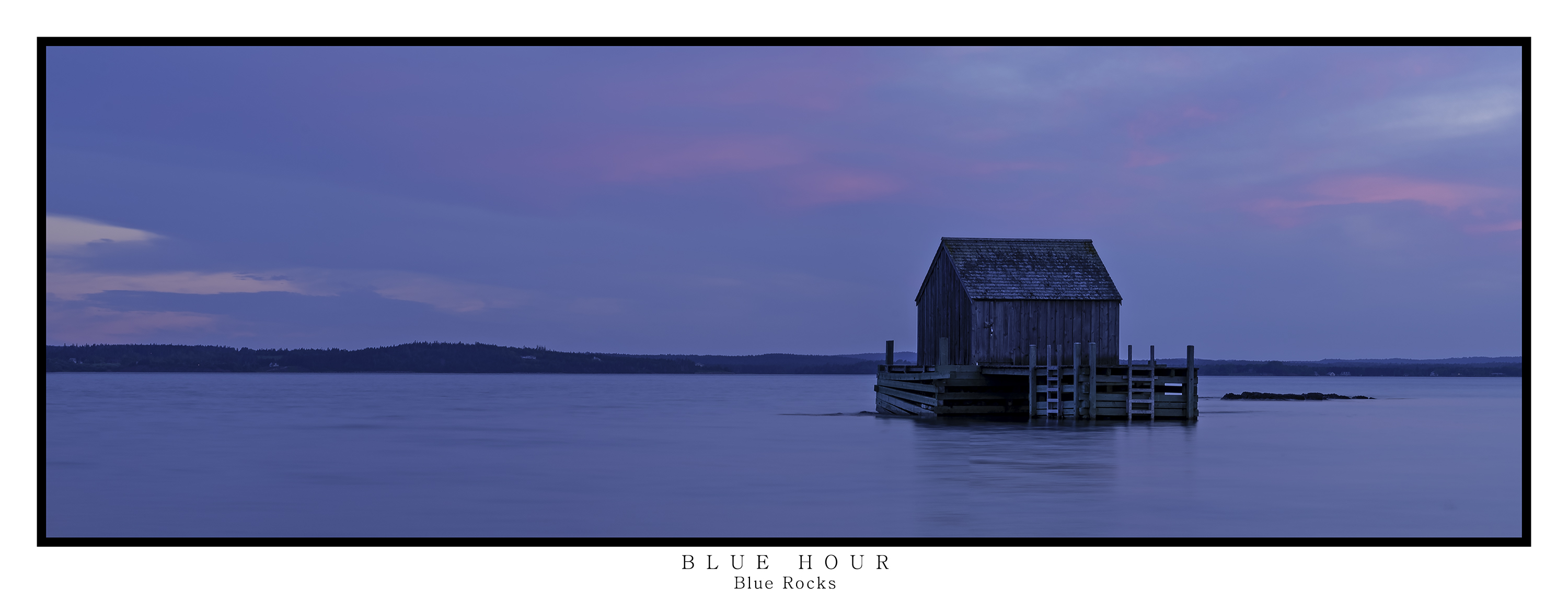 Panoramic landscape of a small old wooden fishing hut on stilts in the sea at high tide, taken at Blue Rocks, Nova Scotia at blue hour as the sun is setting and there is still a hint of pink in the clouds with a calm and flat sea