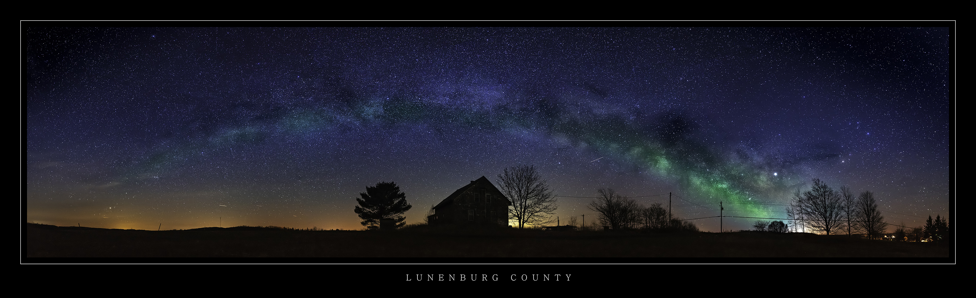 Night time panoramic landscape picture of the Milky Way Galaxy over a silhouetted abaondoned house and trees in Lunenburg County Nova Scotia