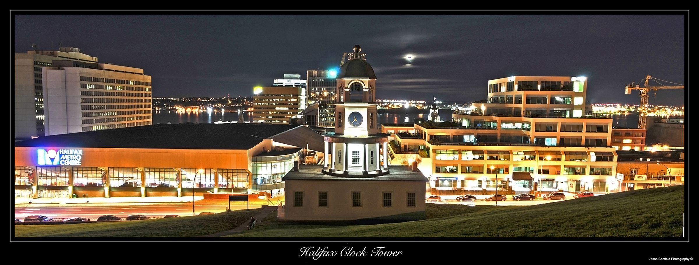 Panoramic nighttime landscape picture of Halifax Citadel clock tower and the moon behind clouds in Halifax, Nova Scotia, Canada.