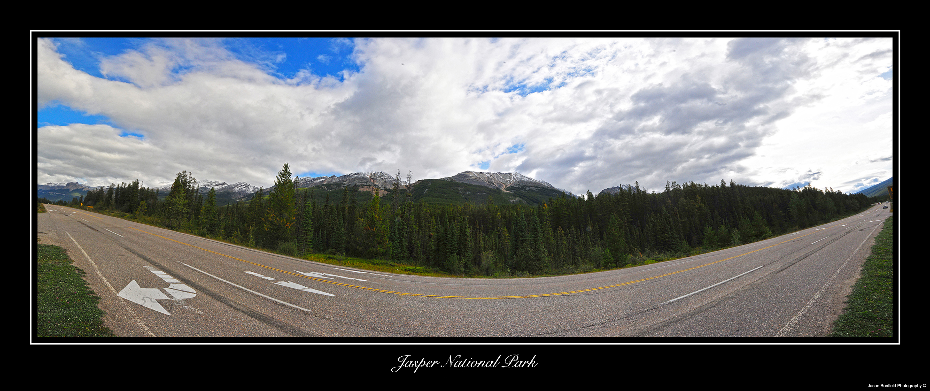 Wide angle,  panoramic landscape picture of a road and mountains with a blue sky with white clouds in Jasper National Park, Alberta, Canada.