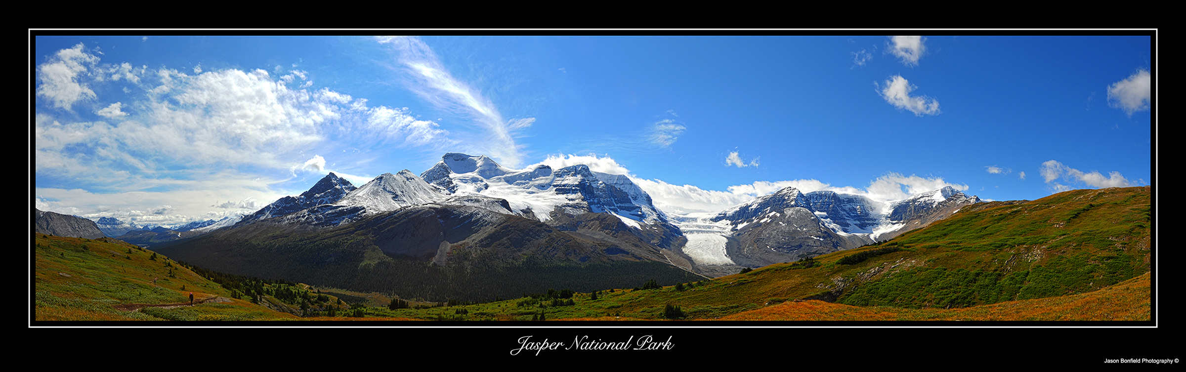 Panoramic landscape picture of mountains, glaciers and blue sky with white clouds in Jasper National Park in Alberta, Canada.