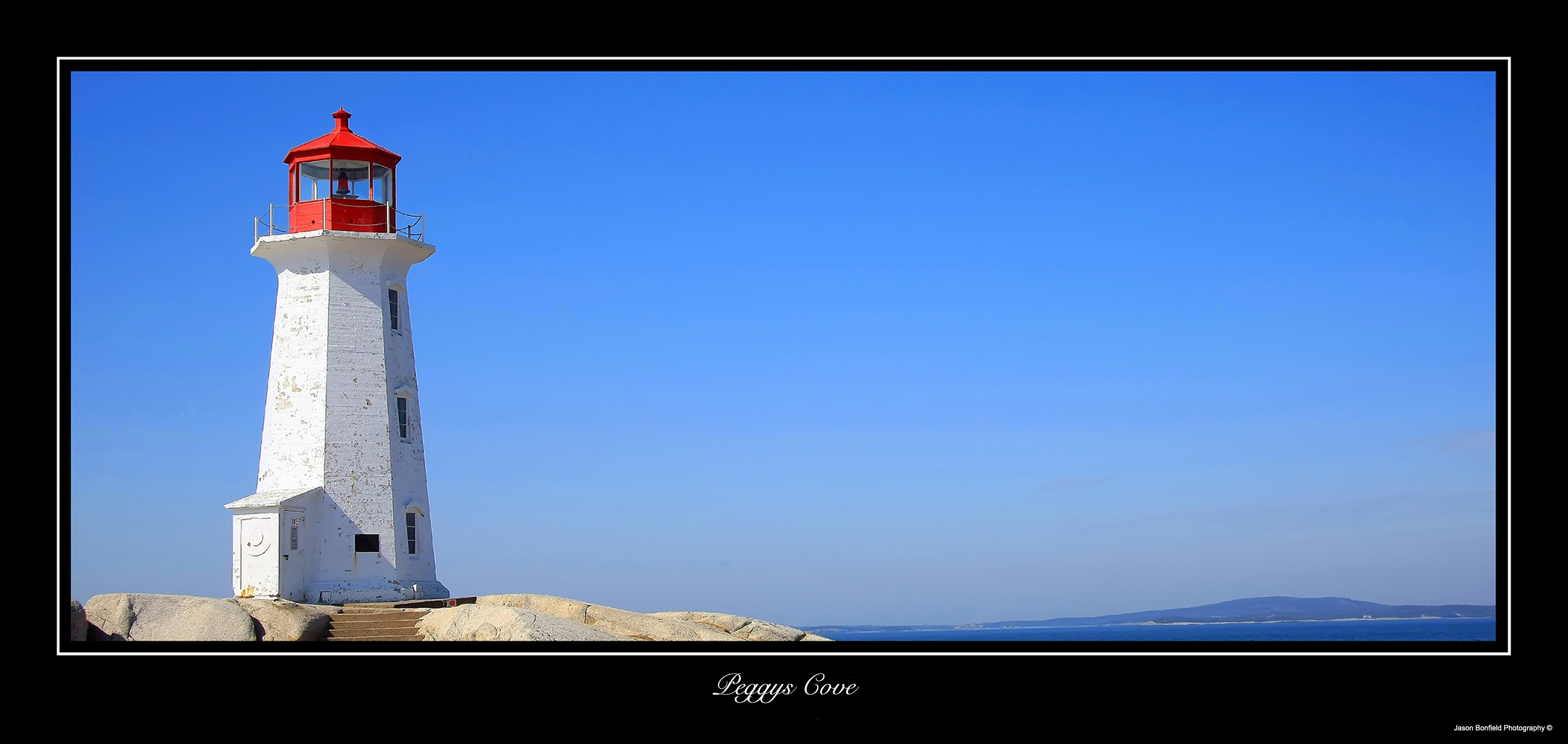Panoramic landscape picture Peggys Cove Lighthouse, Nova Scotia, Canada on a clear blue day.