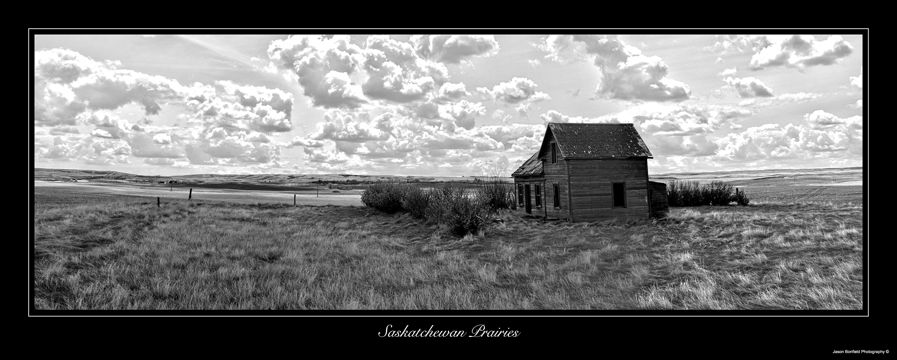 Black and white panoramic landscape picture of an old derelict farmhouse in the Saskatchewan prairies with clouds in the sky in Canada.
