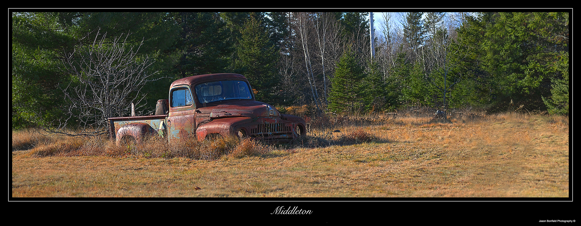Panoramic landscape picture of an old abandoned sidestep pick-up truck, Middleton, Nova Scotia, Canada.