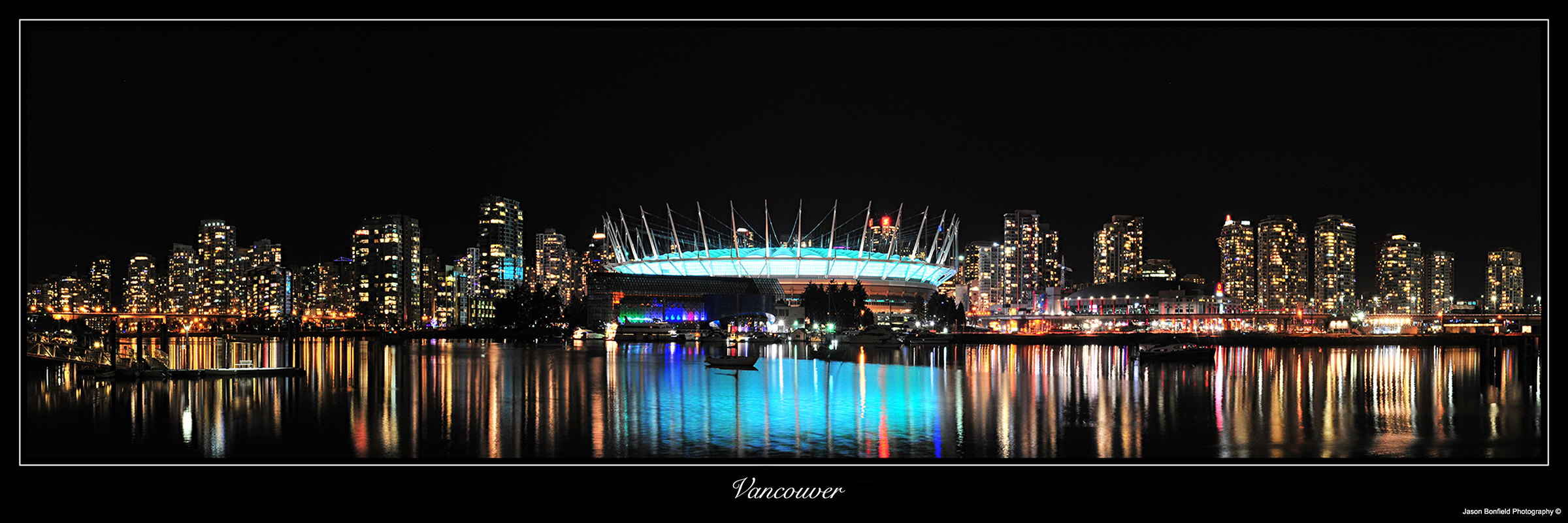 Nighttime panoramic landscape picture of Vancouver City reflected in the waterfront in Vancouver, Canada.