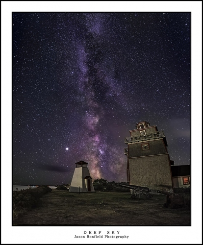 Panoramic lanscape of the Milky Way galaxy rising behind the lighthouse at Point Fort Museum Nova Scotia
