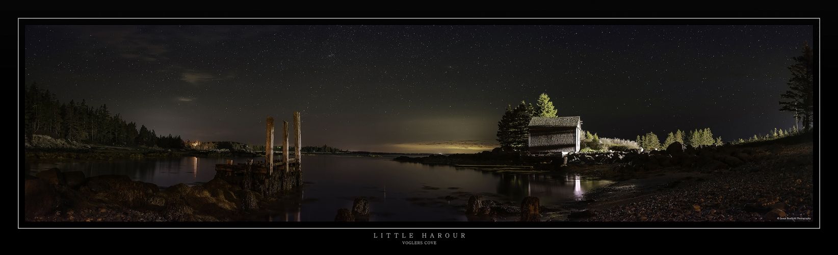 Night time panoramic landscape picture of Little Harbour near Voglers Cover, Nova Scotia South shore, Canada showing an old disused pier with 3 vertical posts and an old fishing hut set against the night sky.