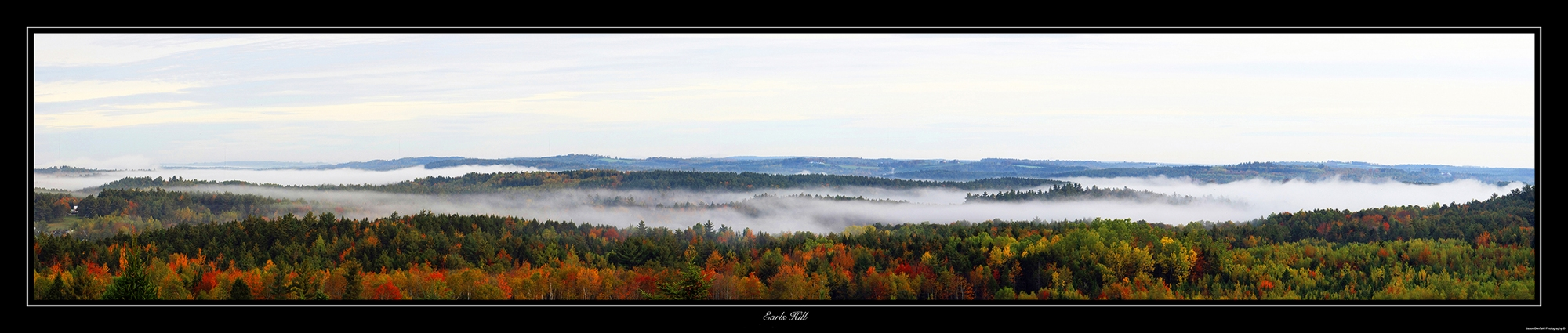 Panoramic landscape picture of Maples trees in autumn with a misty cloud taken in Lunenburg Country, Nova Scotia, Canada.