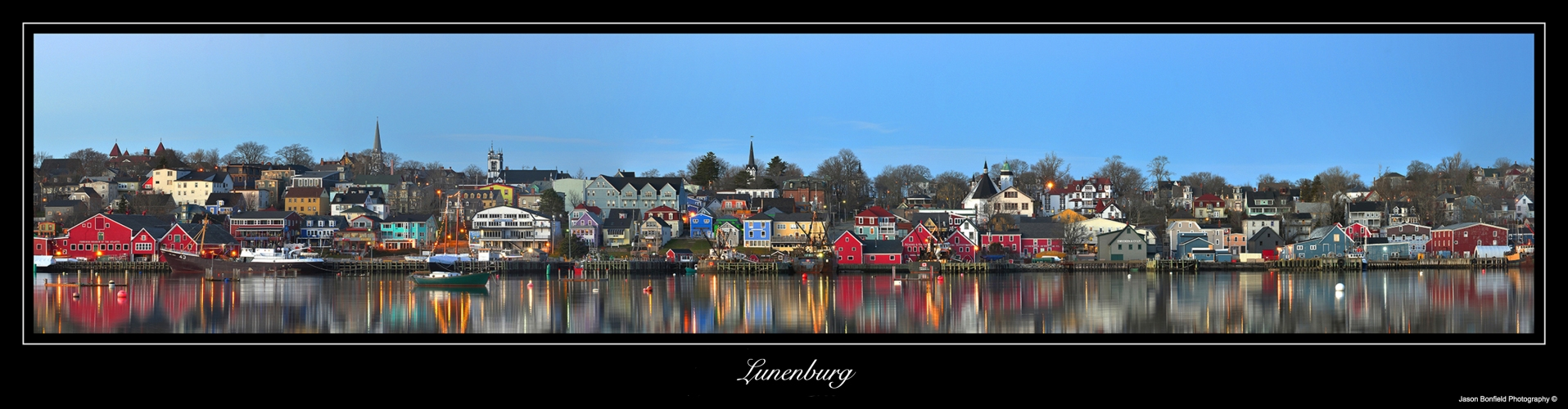 Panoramic landscape picture of Lunenburg town and a clear blue sky reflected in the waterfront in Luneburg County in Nova Scotia, Canada.