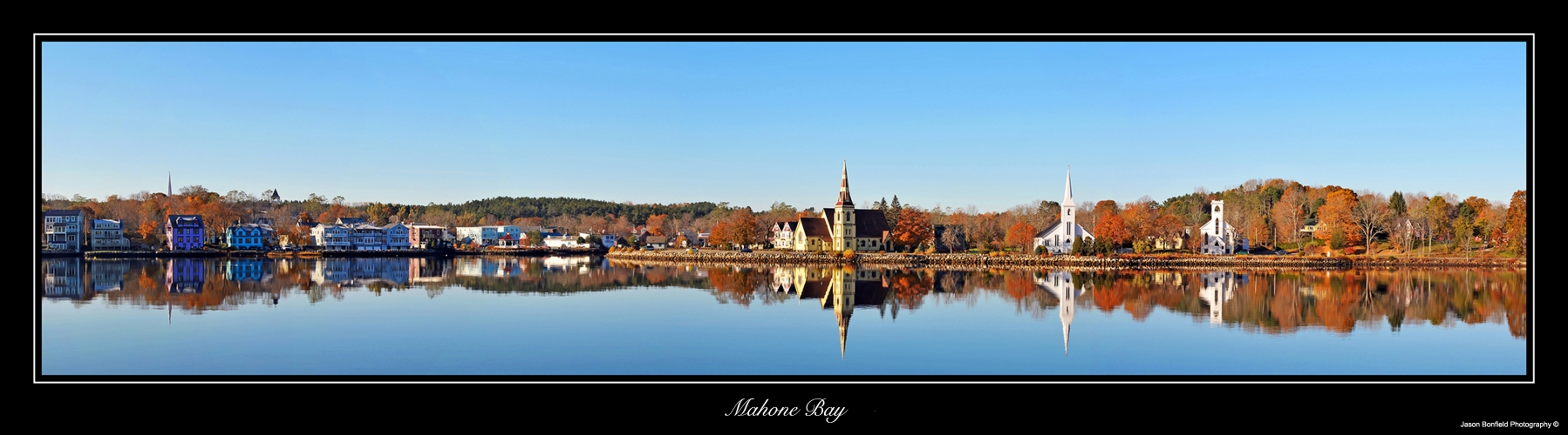Panoramic landscape picture of three churches in Mahone Bay with clear blue sky reflected in the water at Mahone Bay, Nova Scotia in autumn