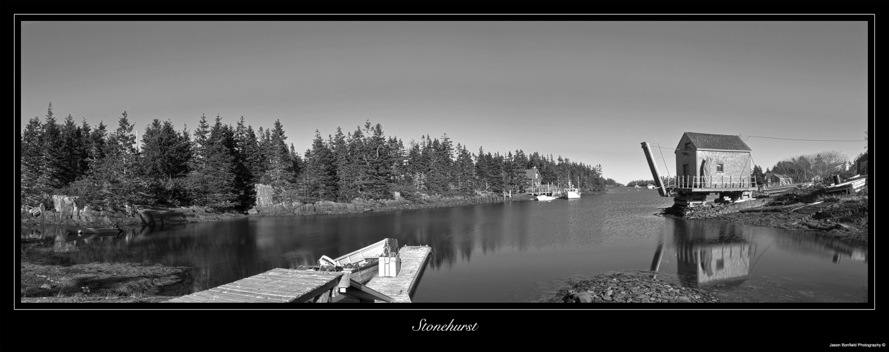 Black and white panoramic landscape picture of a small fishing hut, a jetty and trees reflected in the sea at Stonehurst, Nova Scotia, Canada.