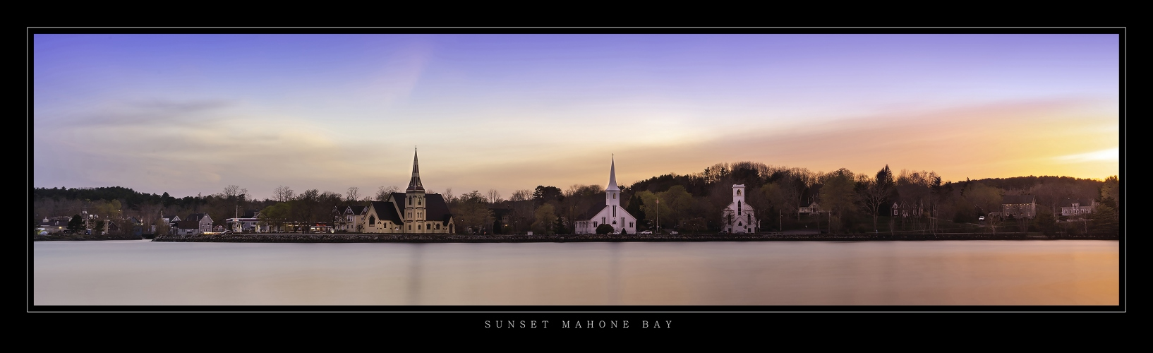 Panoramic picture of the three churches of St. John's Lutheran Church, St. James Anglican Church and the Trinity United Church in Mahone Bay, Nova Scotia at sunset