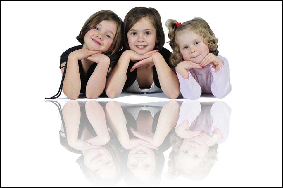 high-key studio picture of 3 girls lying on the ground with a reflection below