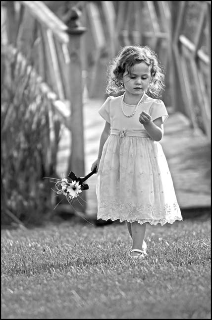 black and white portrait of a young girl in a white dress howling a flower