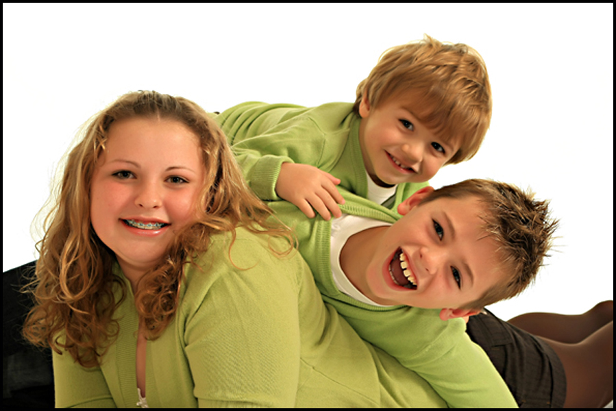 high key family portrait of 3 children in green clothes with smiles against a white background