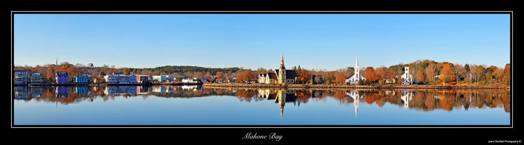 Panoramic landscape picture of three churches with clear blue sky reflected in the water of Mahone Bay, Nova Scotia, Canada in autumn.
