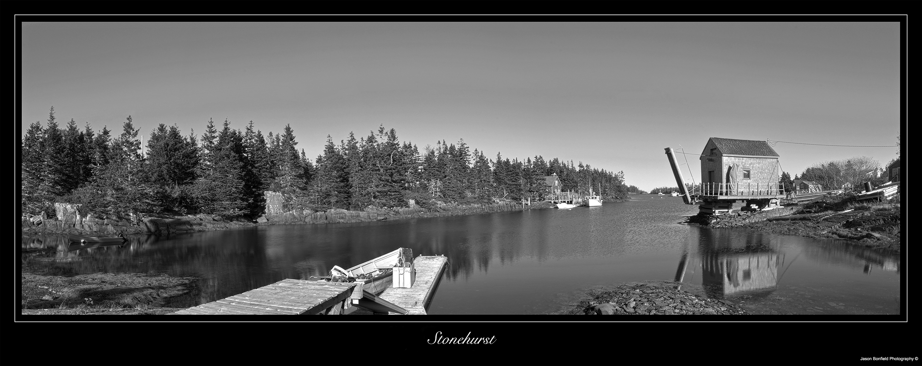 Black and white panoramic landscape picture of a small fishing hut, a jetty and trees reflected in the sea in Stonehurst, Nova Scotia, Canada.